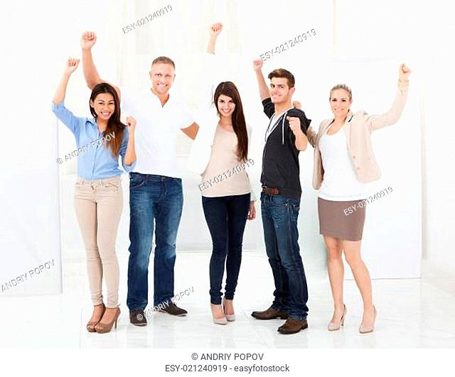 Confident Businesspeople Standing With Arms Raised
