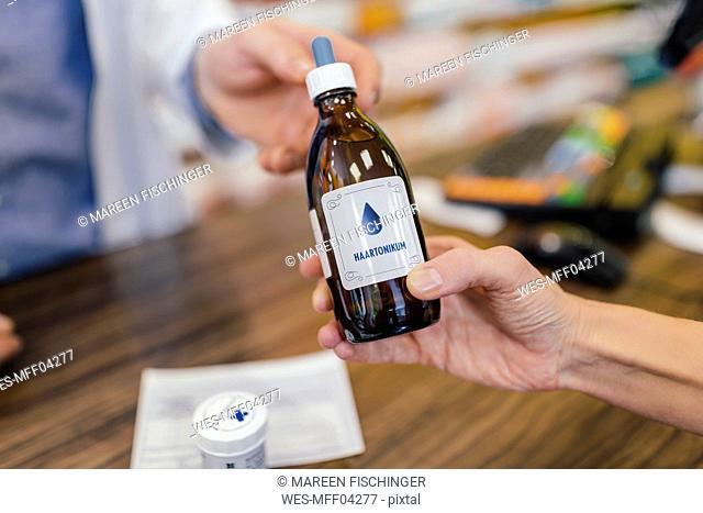 Pharmacist giving medicine to customer in pharmacy