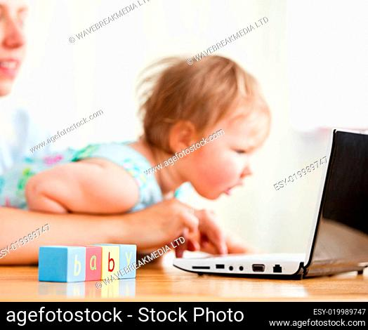 Cute woman surfing on the internet with her girl in the living-room
