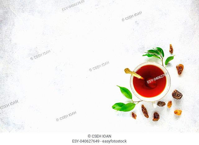 Cup of tea, rock of sugar and fresh green tea leaves, copy space