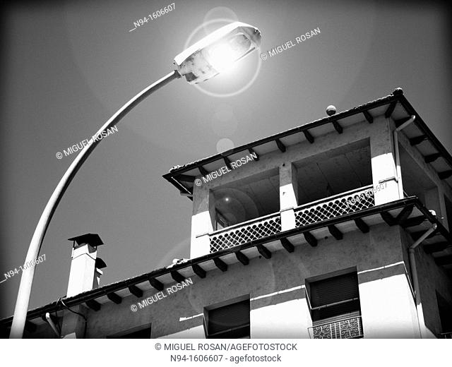 View of the facade of a house lit by street lamps