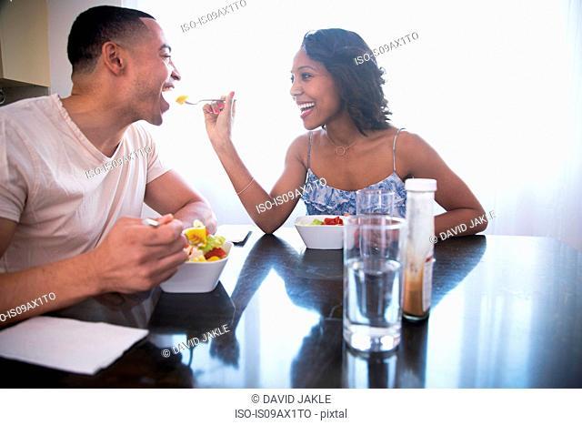 Woman feeding man at dining table