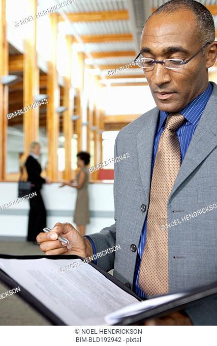 Mixed businessman looking at paperwork