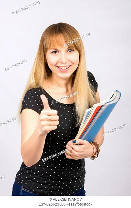 Young woman with folders in hands happily smiling and showing thumb