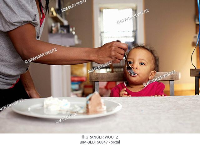 Parent feeing daughter cake at table
