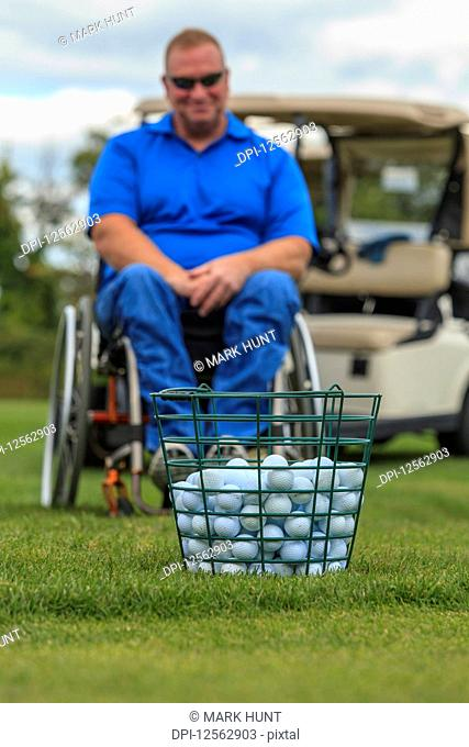 Man in wheelchair with spinal cord injury waiting to play golf