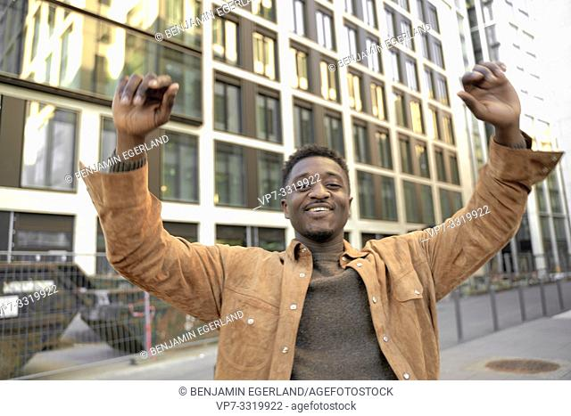 smiling African man with arms up in business district of city, in Frankfurt, Germany