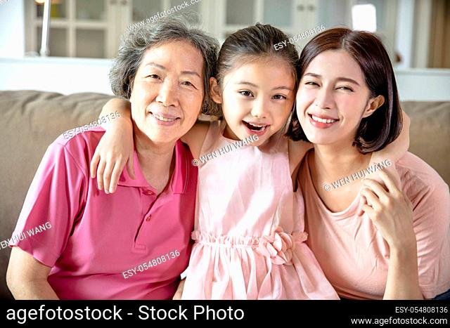 happy grandmother and daughter with granddaughter at home