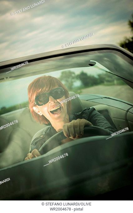 Excited woman enjoying driving her convertible car
