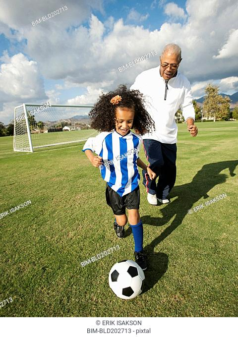 Man playing soccer with granddaughter