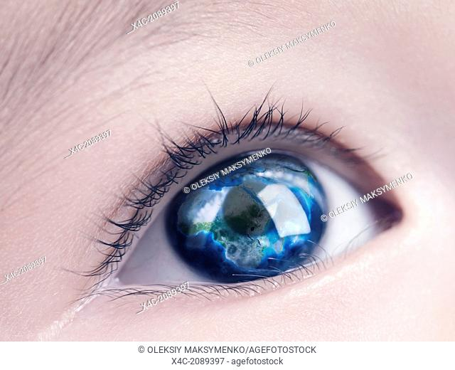 Closeup of a child's blue eye with the Earth globe, world map reflecting in it