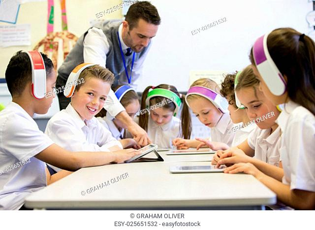 Group of children wearing colourful wireless headsets while working on digital tablets, the teacher can be seen supervising the students in the classroom