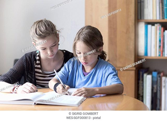 Sister helping her little brother by doing his homework