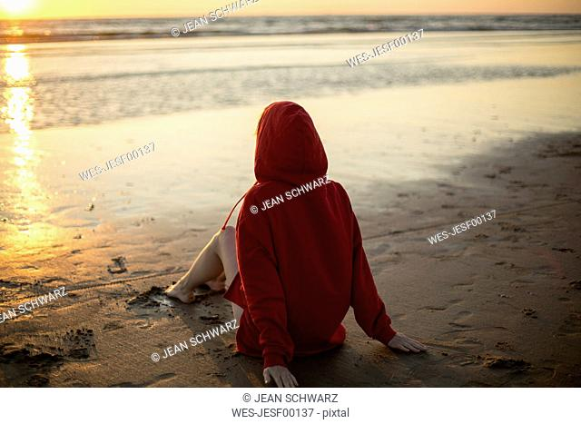 Young woman wearing red hooded jacket sitting on the beach at sunset