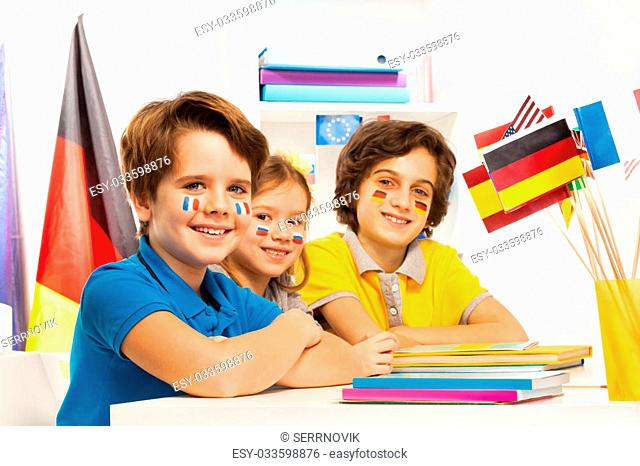 Three happy children with flags on cheeks sitting at the classroom and studying geography