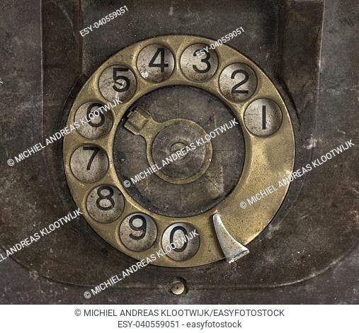 Closeup of vintage telephone dial, scratched and filthy