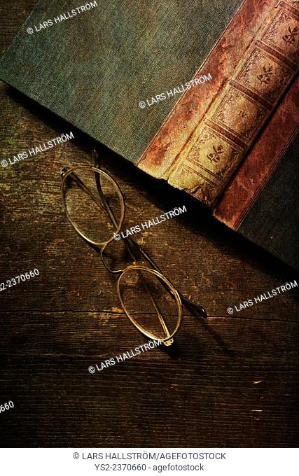 Still life with old book and glasses on wooden table. Top view