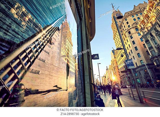 Telefonica buliding reflection on a window shop poster in Gran Via Avenue. Madrid. Spain