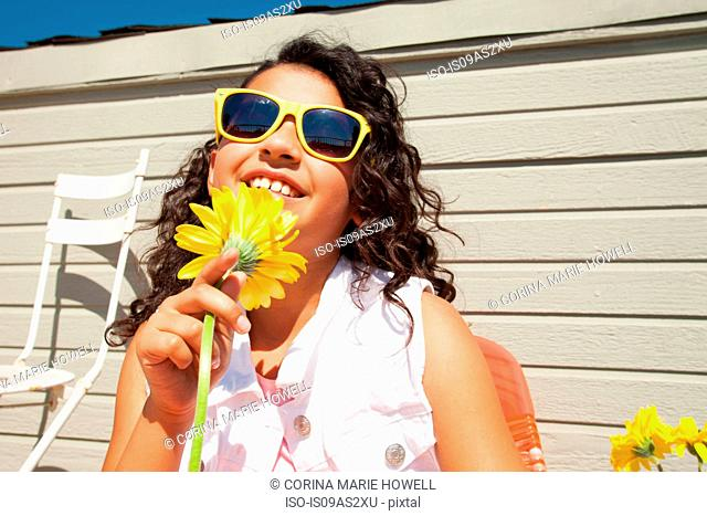 Portrait of girl wearing yellow sunglasses holding sunflower on patio