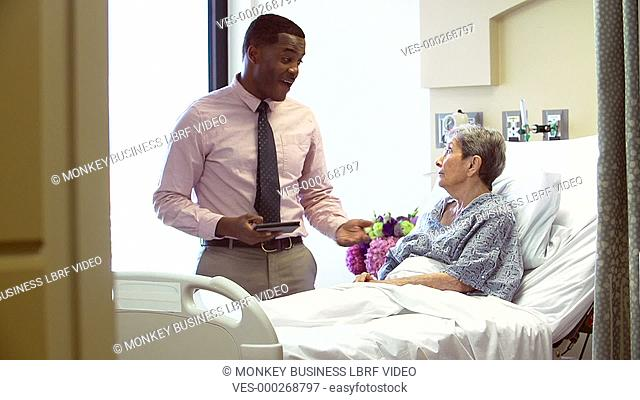 Doctor with digital tablet visiting senior female patient in hospital bed to discuss case.Shot on Sony FS700 in PAL format at a frame rate of 25fps