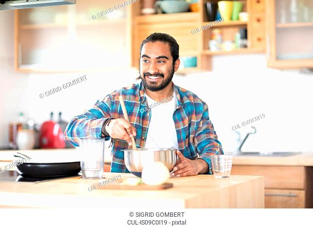 Young man at kitchen counter preparing food in mixing bowl