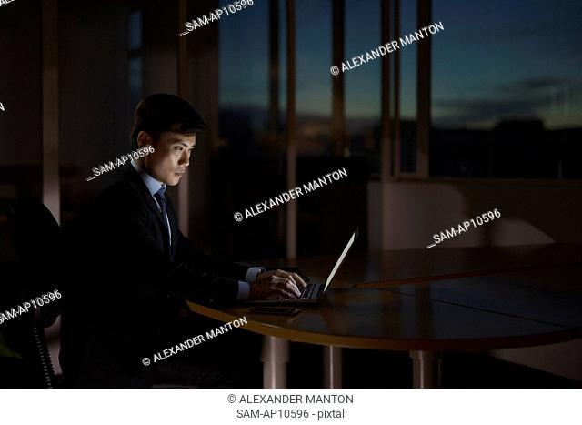 Singapore, Businessman at desk using laptop at night