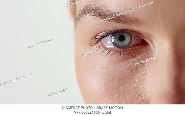 Close-up of a woman crying with tear falling from her eye