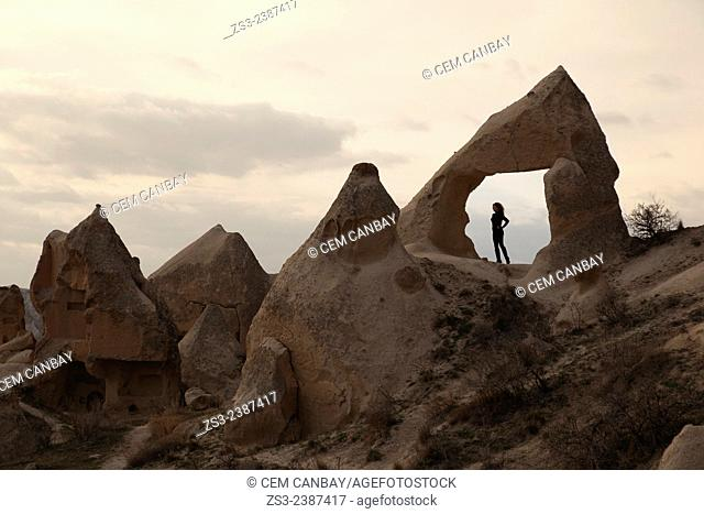 Woman walking near the fairy chimneys and rock formations in Goreme, Cappadocia Region, Nevsehir, Central Anatolia,Turkey, Europe
