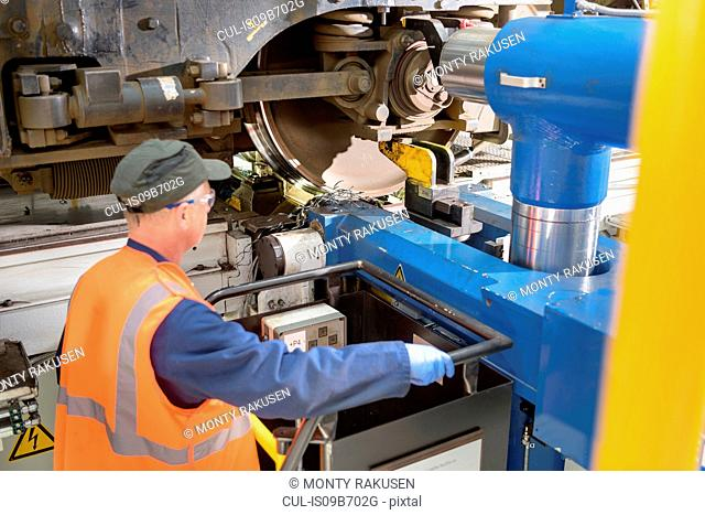 Engineer with locomotive wheel lathe in train works