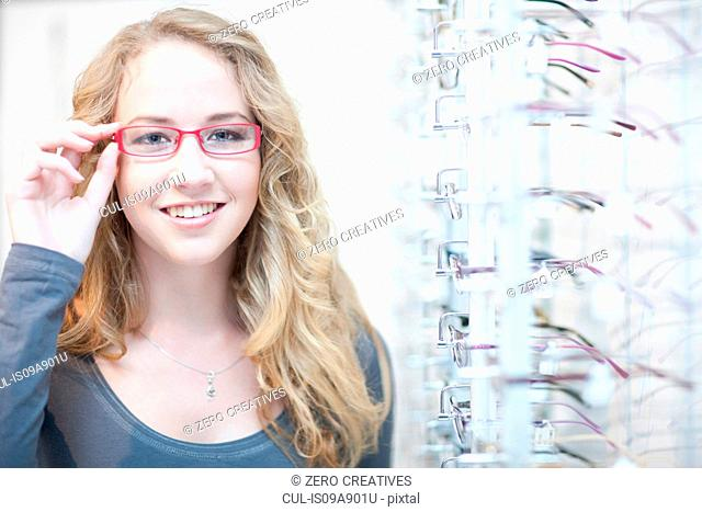 Young woman trying on eyeglasses