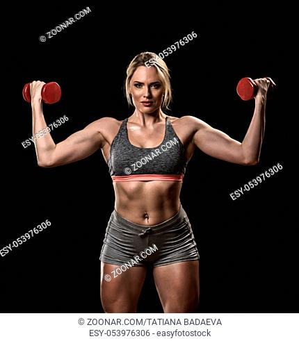 Beautiful muscular woman lifting dumbbells isolated on black background
