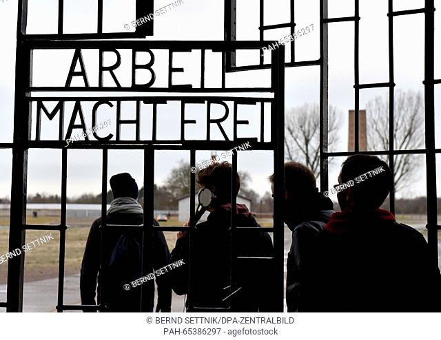 Visitors walk through the gate of the former Sachsenhausen concentration camp, which bears the words 'Arbeit macht frei' (work sets you free'), in Oranienburg