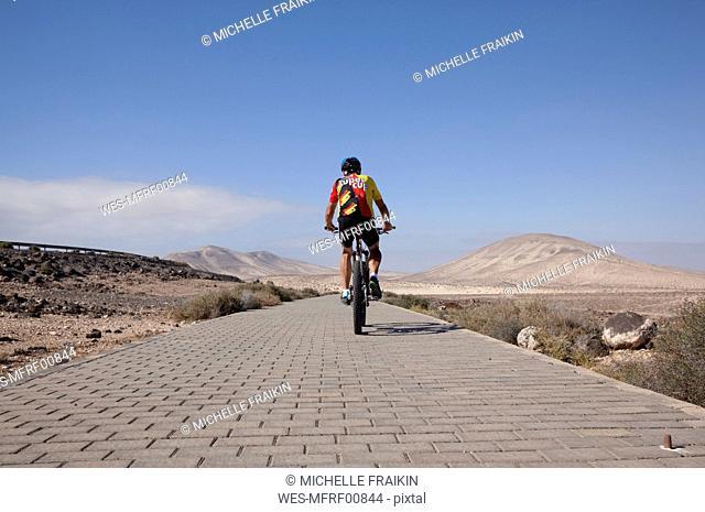 Spain, Canary Islands, Fuerteventura, senior man on mountainbike