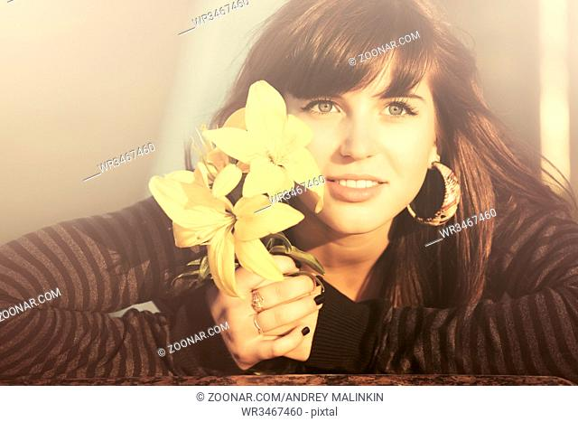 Happy young woman with flowers smiling outdoor