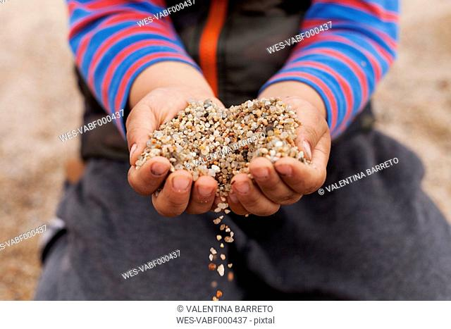 Hands of little boy holding sand, close-up