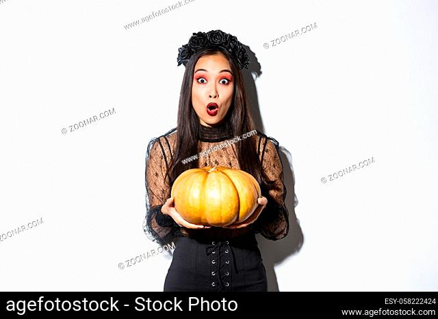 Surprised asian girl in witch costume, holding pumpkin and gasping amazed at camera, preparing for halloween holiday, standing over white background