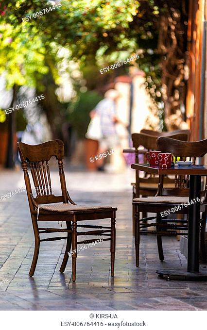 Street view of a empty coffee terrace with tables and chairs in old town of Antalya, Turkey. Small depth of field