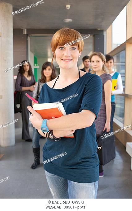Germany, Leipzig, Women smiling, students standing in background
