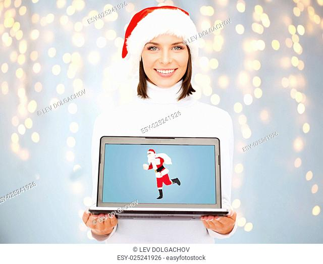 christmas, holidays, technology and people concept - smiling woman holding laptop computer with santa claus picture on screen over lights background