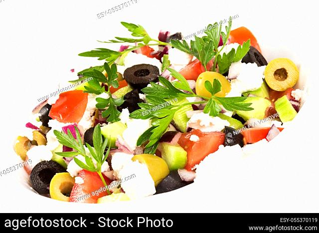 Colorful fresh Greek salad is in white dish on white background