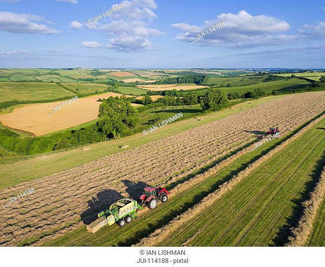 Aerial View Of Tractors Baling Hay In Field