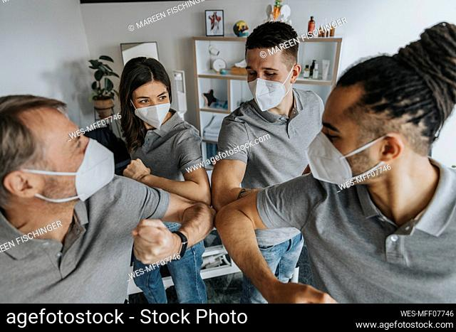 Male and female physiotherapists doing elbow bump during COVID-19