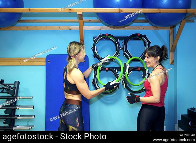 Two women look at each other and laugh awith extended arms a at the gym. They are also using exercise mats