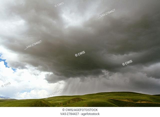 The view of the storm on the grassland in the daytime