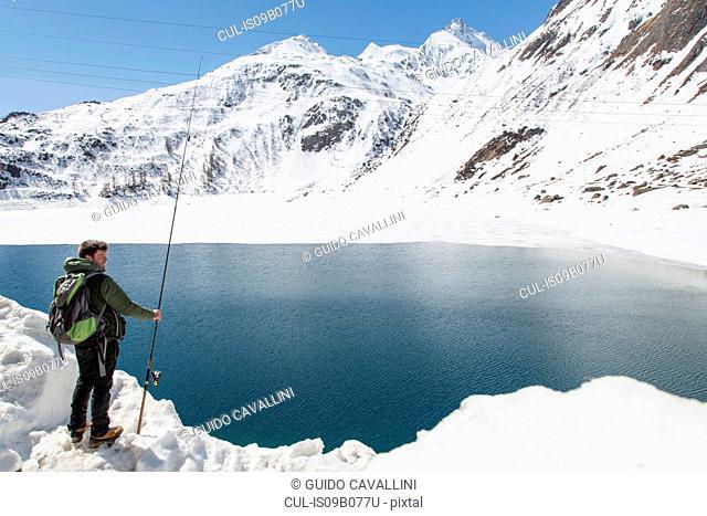 Mid adult man, fishing, Morasco lake, Morasco, Val Formazza, Piemonte, Italy