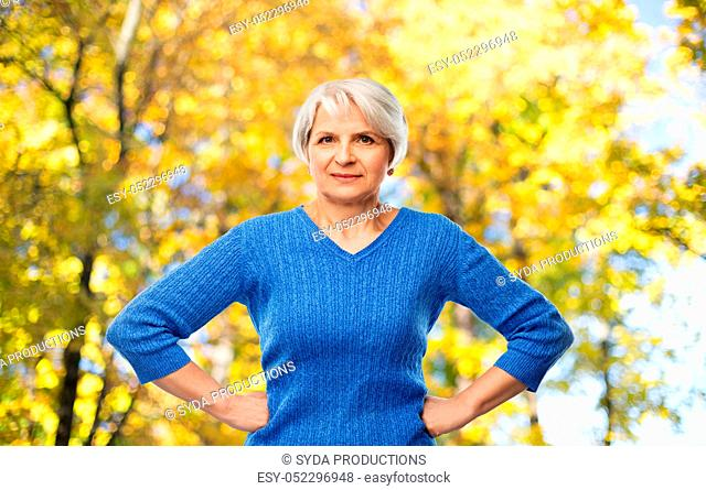 senior woman with hands on hips in autumn park