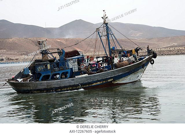 Fishing boat laden down with supplies with barren Moroccon landscape behind; Sidi Ifni, Morocco