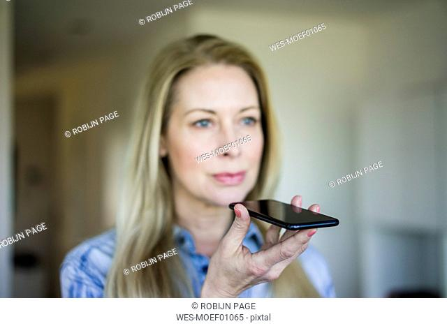 Businesswoman using cell phone, close-up