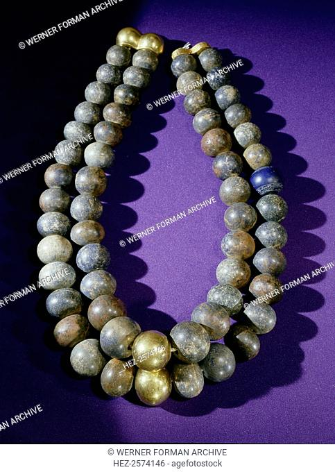Necklace of double strands of lapis lazuli beads, with gold clasp and two gold beads at centre. From the tomb of Psusennes I