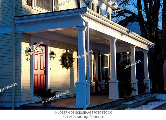 Example of home architecture showing a front porch with a red door and a holiday wreath on a house in Lunenburg, Nova Scotia, Canada